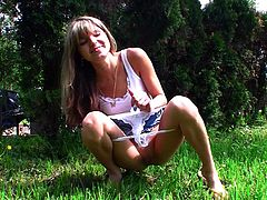 Stunning babe Gina is pissing on the grass