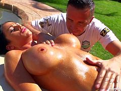 Dark haired and busty babe with an amazing tanned body enjoys in hot and sunny day and gets her body oiled and massaged by Keiran Lee and his skillful hands