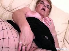 Kinky mature in fishnets strips and rubs her hairy fat pussy
