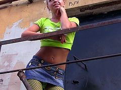 Hilarious and nasty blonde teen in green pantyhose is showing her panties in the public