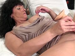 This mature lady has a big dildo and she's not afraid to use it. Watch her spreading those thighs really wide and playing with her shaved pussy. She enjoys herself and the thought we are watching her acting like a slut makes the brunette hornier. Keep on watching and see how she will fuck herself