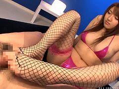 Fishnet Japanese cutie gives a hot footjob to some kinky man