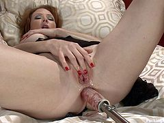 Click on this hot video and you'll see a smoking hot redhead pleasing her pink pussy with the help of a fucking machine as she lays back on a bed.