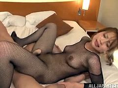 Slutty Japanese milf wearing a fishnet bodystocking is playing dirty games with two men indoors. She sucks their shafts hungrily and then allows the dudes to destroy her tight Asian cunt.