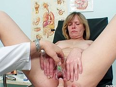 Delicious granny sits in the gynecological chair while a rapacious doctor widens her pussy with speculum before he starts poking her with dildo.