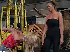 young slender blonde babe with long hair and natural boobs in sexy outfit gets tied up in uncomfortable position and tortured by black haired milf with huge firm hooters in bondage fantasy