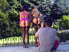 Long haired blonde Sandy and her black haired girlfriend Mya Diamond in lingerie and high heels teases and pose outdoor and share black bazooka in living room at photo shoot