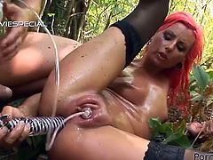 It doesn't get kinkiest and weirdest than this. The red-haired slut will get her pussy pumped and her asshole fucked by toys and cock outdoors in the woods.