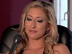Young looking naughty young blonde slut Karina Shy with big tempting hooters and sexy body figure in black short dress answers questions at arousing interview filmed in close up