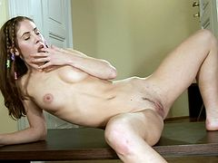 Sexy girl undresses and shows her hot nude body lying on the table. After that she takes a dildo and stuffs her vagina.