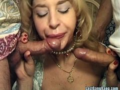 Check out this vintage scene where a busty blonde milf ends up with her mouth filled after being double penetrated by big cocks in a threesome.