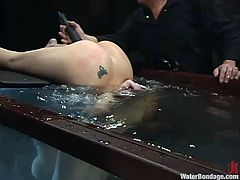 Hot chick with big boobs and ass gets her pussy drilled by the fucking machine. Then the guy chains this bitch and puts her into the water.