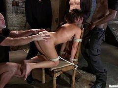 Astounding brunette chick is having fun with a few men in some dark place. The guys tie the girl up and fuck her mouth, pussy and asshole deep and hard.