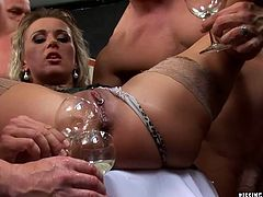 Group of perverse muscular dudes surround a filthy blond mature that lies on table with legs spread aside. They put glasses to her ruined pussy for her to piss in it and later drink her own urine in insane gangbang sex video by Tainster.