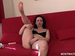 Brunette mature in lingerie teasing her starved cunt on the sofa