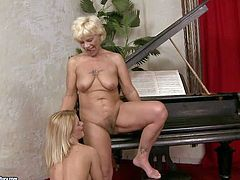 Short haired mature blonde whore with hanging tits in red undies and smoking hot young long haired babe with delicious ass lick each other in kinky fantasy by black piano