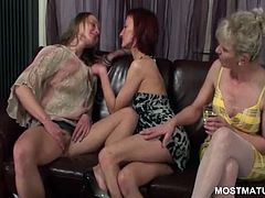 Three mature lesbians kissing and making out on a leather couch