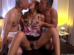 Sexy Japanese bitch is having fun with two dudes in a bedroom. She sucks their cocks and then lets the men double penetrate her.