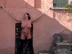 She's been bad girl so now she meets her punishment. Mature slut is crucified along the wall outdoor. She stands totally naked under the open sky.
