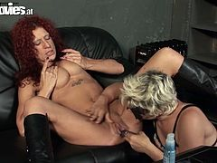 Mature lesbians are scissoring on a bed having dildo in their cunts