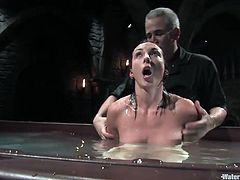 This is an extreme bondage scene featuring a kinky brunette and a perverted sadist with a fish tank he's gonna dip her in.