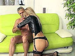 One of a kind blonde bombshell Mandy Dee with big hooters and long hair in leather black outfit and lingerie gives head to her lover and rides on his cock.