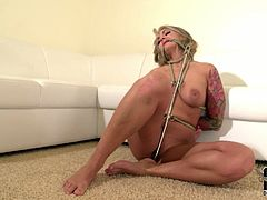 Kinky blondie with tattooed back gets tied up with ropes. She's got no choice to get rid of these tight ropes. Kinky chick with smeared makeup gets also a metal hook into her asshole. She moans and cries of delight and pain at once.
