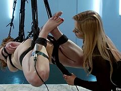 This extreme bondage video has a girl strapped in a way she hangs from the ceiling and then gets toyed and is forced to eat pussy.