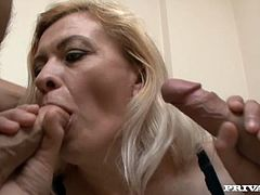 Nasty mature blonde is having fun with two guys in the living room. She sucks their dicks passionately and then welcomes them in her juicy cunt and gets fucked in cowgirl position.