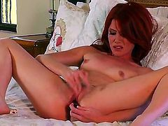 Young naked redhead babe Elle Alexandra with small natural boobies spreads long sexy legs and stuffs her wet pussy with glass dildo in provocative positions in bedroom.