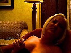 Busty blonde loves to stroke her wet vag while smoking and moaning