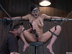 Tied on a metal frame with chains the brunette is being pleasured and teased by her executor. He plays with her pussy and then whips it hard and merciless. The fucking slut can't even scream as she is mouth gagged with a funnel. She was a very bad girl and deserves more then a rough pussy fingering and rubbing.