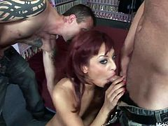 Filthy red-haired bitch stands on her knees in front of two rapacious dudes to oral fuck their sturdy cocks in turns before she gets fucked in doggy and cowgirl positions.