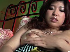 Flamboyant Japanese babe lies on her back wearing a sultry lingerie while stroking her soaking vagina with fingers before she pounds it with dildo in steamy solo sex video by Jav HD.