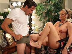 Sexy blonde milf actress Simone Sonay is in her dressing room getting ready to film. Her costar is in their with him and she rubs her feet over the crotch of his pants. He pulls down his trousers and she rubs her feet on his underwear. He sucks on her toes and pulls her panties off to eat her cunt.