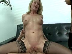 Horny blonde chick in stockings licks the pussy and then lies down on a sofa. She spreads her legs and gets fucked in her ass with strap on.