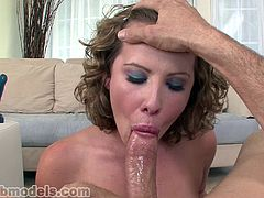 Curly-haired brunette is sucking a dildo
