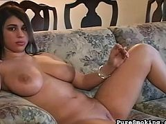 Brunette with big tits likes posing her nude body while smoking and undulating