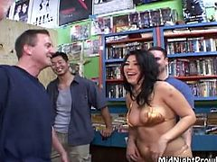 Flamboyant brunette mom in tiny gold bikini walks around the grocery store full of sex hungry dads before she kneels down to mouth fuck their stiff cocks in turns in gangbang sex video by Pornstar.