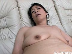 Lewd Japanese mom is having fun with some guy in the living room. She shows him her flabby tits and then moans with pleasure while jumping on his hard prick.