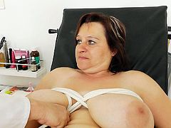 Chubby mom with huge natural jugs is lying on a couch with her legs wide open. Perverted Doc opens juicy pussy lips exposing deep bosomy red cave. Then he ties up her saggy huge boobs with rope.