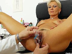 Filthy mommy is examined by perverted Doc in medical office. She sits on a special chair with her legs wide open letting the guy do kinky shit with her beef curtains. So, Doc opens pussy lips wide showing pink vagina in all the glory. He also stuff the cunt with speculum stretching the hole wide as hell.