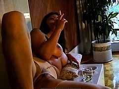 Posing her big tits and playing with her pussy while smoking makes her very horny