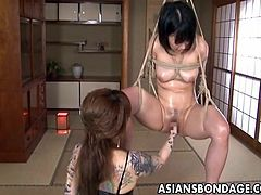 This hot Asian babe is tied up and suspended with her legs open.  Her lesbian mistress takes her fist and fucks her captors tight cunt.