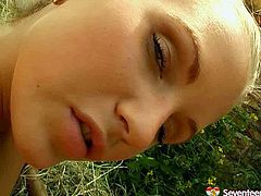 Blonde doll is lying on a hay outdoor. She is barely naked demonstrating her goodies. Then she stuffs vaginal opening with smooth sex toy drilling her twat deep.
