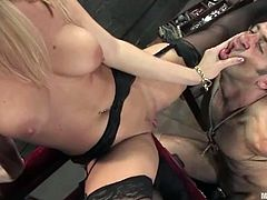 Curvaceous blonde girl in latex corset chains a guy and whips him with a stick. After that she also orders him to lick her vagina.