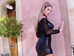 Yummy blond hottie appears on screen wearing black leather dress that is tracing her tempting curves. She poses on cam standing along the wall. Sexy blondie slips her hand under the dress caressing her pussy. She shows her treasure close-up to the cam.