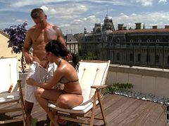 Bettina Dicapri is a black haired hot girl in bikini and shades. She gives blowjob to tattooed well built guy in the sun. She gievs head and bares her natural tits on the roof.