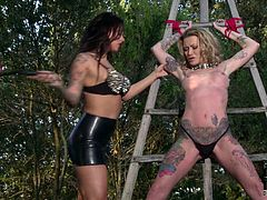 Sextractive blonde mommy fully covered with ink has got gorgeous body shape. She is tied up outdoor in the garden. Tough mistress in sexy leather outfit is whipping her hostage. X-rated scene that is able to blow your mind.