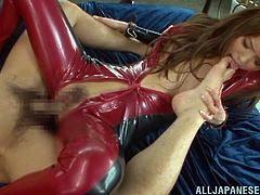 Lewd Japanese chick Emiri Okazaki wearing a latex overall is having fun with some dude in the bedroom. She sucks his prick hungrily and then allows him to fuck her cunt doggy style.